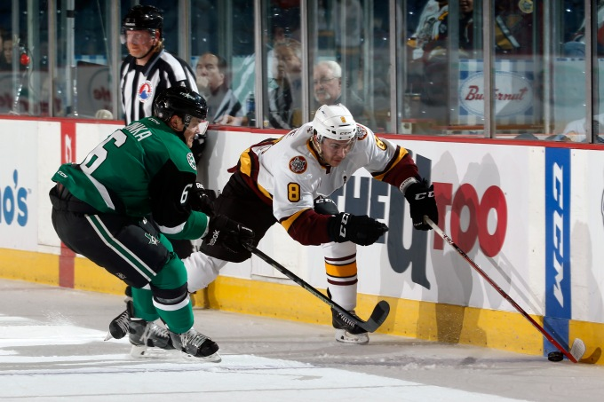 Julius Honka and Ty Rattie battle for a puck.